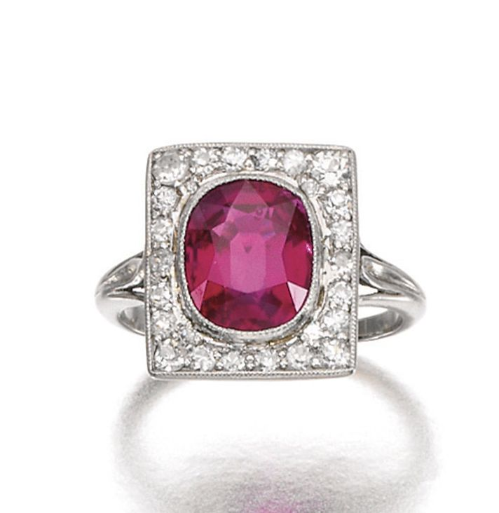 RUBY AND DIAMOND RING, CIRCA 1900. Set to the centre with a cushion-shaped ruby weighing 2.60 carats, inset to a rectangular plaque accented with circular- and single-cut diamonds
