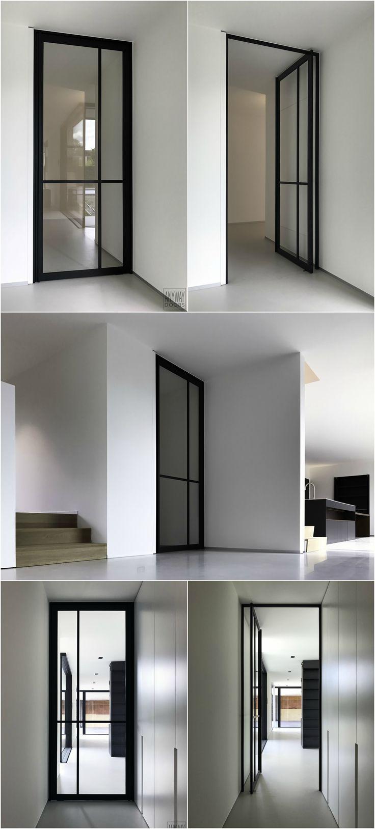 Pivoterende stalen deur van ANYWAYdoors. Deze deur wordt volledig op maat gemaakt van zwart geanodiseerd aluminium in combinatie met een pivotscharnier waarvoor niets in de vloer ingebouwd dient te worden.