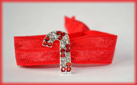 This festive red elastic hair tie has a sweet candy cane rhinestone slider. This fancy hair tie is perfect for your holiday parties, but can