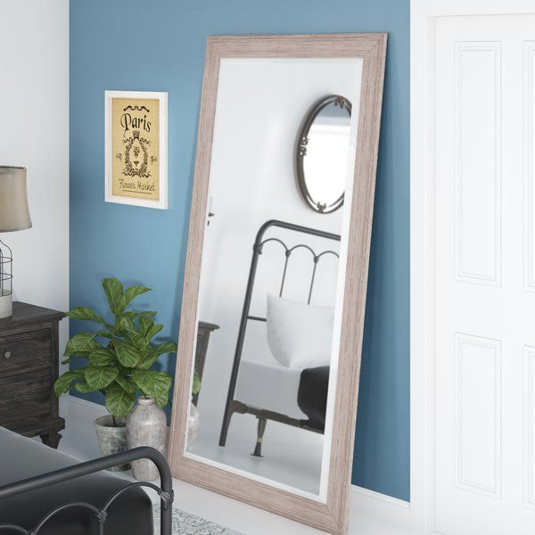 At six and a half feet tall, this generously sized mirror leans against your wall and makes getting ready in the morning easier. Its full-length beveled glass lets you check out your reflection from head to toe, while its wood frame balances out the sleek design with a touch of warmth. This versatile piece features a distressed, white wash finish that complements most color palettes and gives it a rustic look.