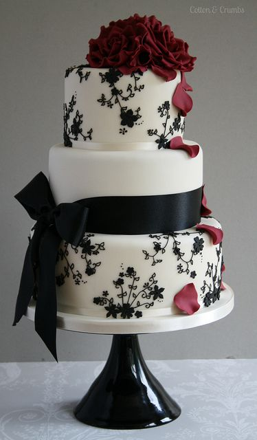 Black, white & red wedding cake with black ribbon accent.