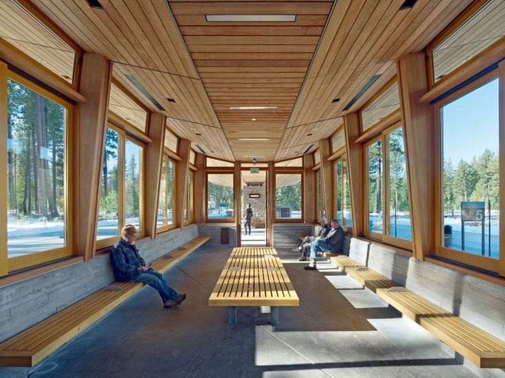 Inclined wood ceiling + plain concrete floor + wood benches + tall windows integrated with tapered wood roof supports ~via contemporist Tahoe City Transit Center by WRNS Studio