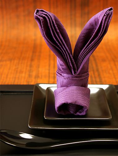 Japanese napkin fold .. Rabbit's Ears ... purple on square black plates ... delightful!!