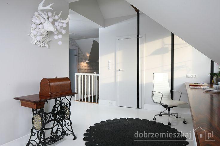 Cześć poddasza przeznaczona do pracy. Proste , minimalistyczne formy i kolory dopełniają detale : żeliwne nóżki stołu starej maszyny do szycia ,  fotel biurowy, biały jeleń na ścianie