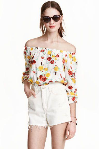 Korte off-the-shoulderbloes: Een korte bohemien bloes van geweven crêpekwaliteit. De bloes komt tot in de taille en heeft elastiek aan de halsuitsnijding, aan de onderkant en onder aan de mouwen.