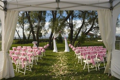 outdoor wedding gazebo and white wedding arch with rose petals in the center walkway aisle and white chairs with pink bows