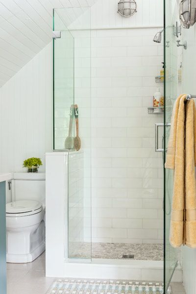 A subway-tiled shower enclosed with frameless glass makes for a functional  and unfussy bath