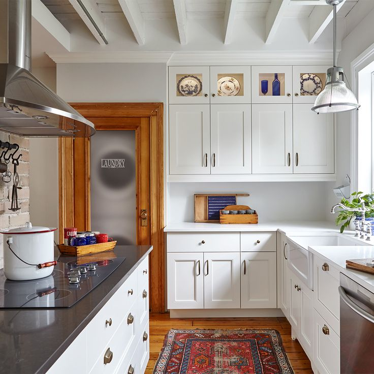 Charming little white kitchen with its vintage decoration. The wood accents and the farmhouse sink gives a nice touch. By Square Footage.