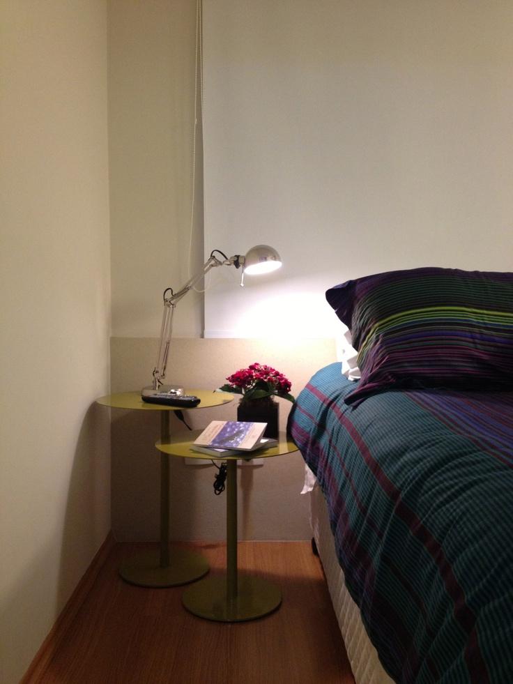 Mesas de tamanhos diferentes fazem a vez do tradicional criado-mudo ao lado da cama.