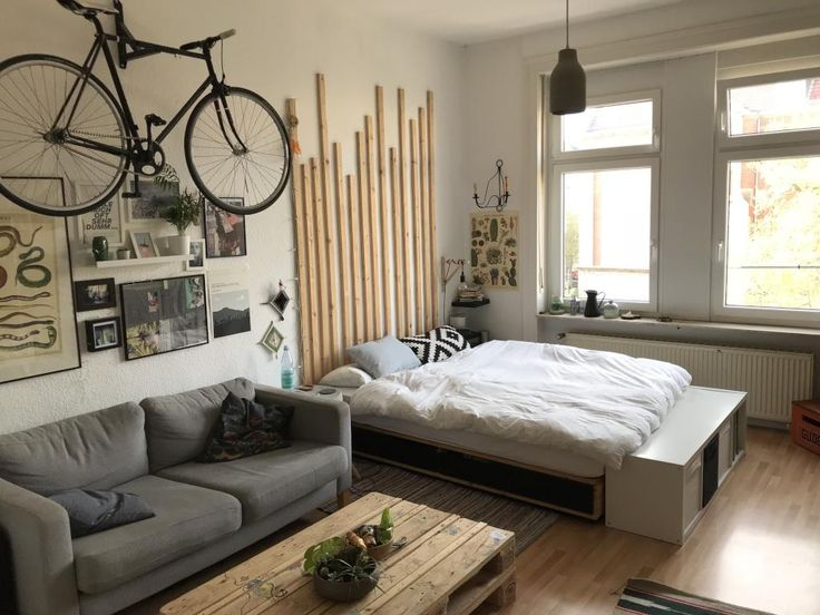 Cool furnishing idea for a shared flat with sofa, coffee table, bed and bike at …