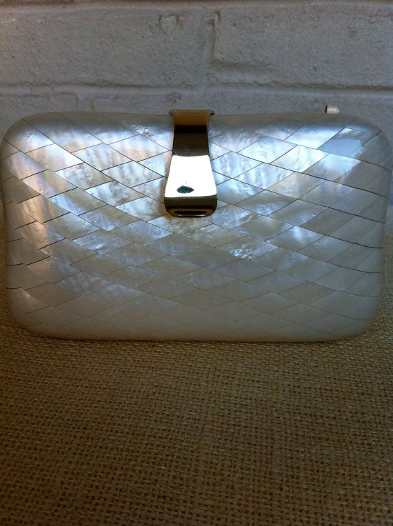 Vintage mother of pearl nacre handbag. Beautiful cream color and gold tone accents. The outside is i great condition with a small scratch on the bottom. There is some rust on the chain and on the inside lining (I think this is from storing the chain inside the purse.) I have not tried to remove the rust. Tag reads: Aspects Hong Kong It doesnt close completely-I think because of the chain, but is still a gorgeous piece-perfect for holiday parties