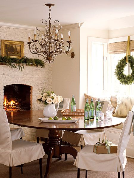 Dining area with warm fireplace; love the white brick and bronze crystal chandelier!