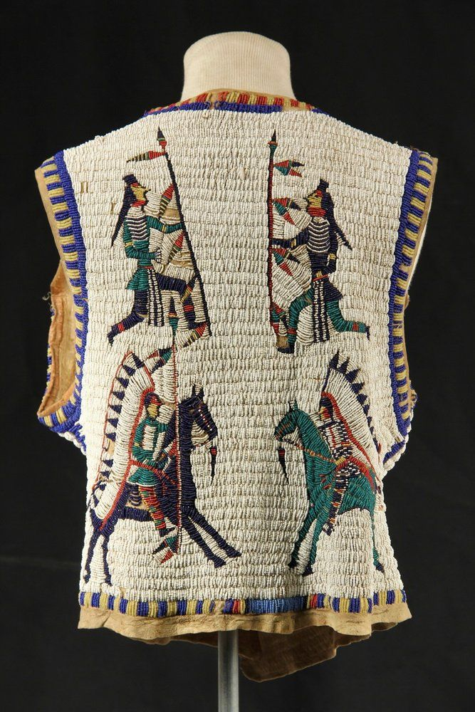 Back view SIOUX BEADED PICTORIAL VEST - Circa 1890-1910 Man's Vest in glass beadwork over brain-tanned deer hide, having a white ground with parti-colored banded edges, and featuring two marching soldiers bearing American flags on front; two warriors on foot and two chiefs on horseback on reverse.