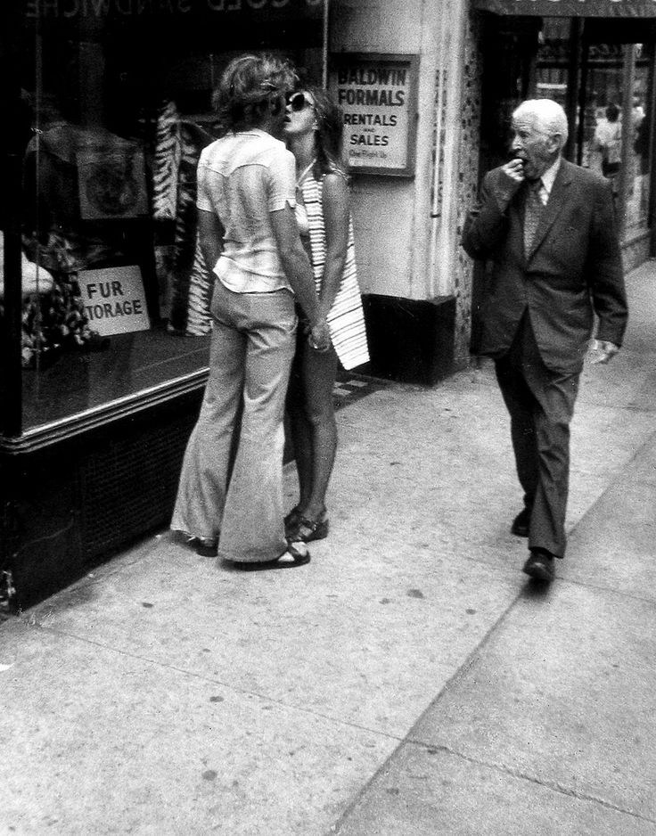 Couple Kissing On Street, Man Walking By  . 1970 . Photo by Leon Levenstein.