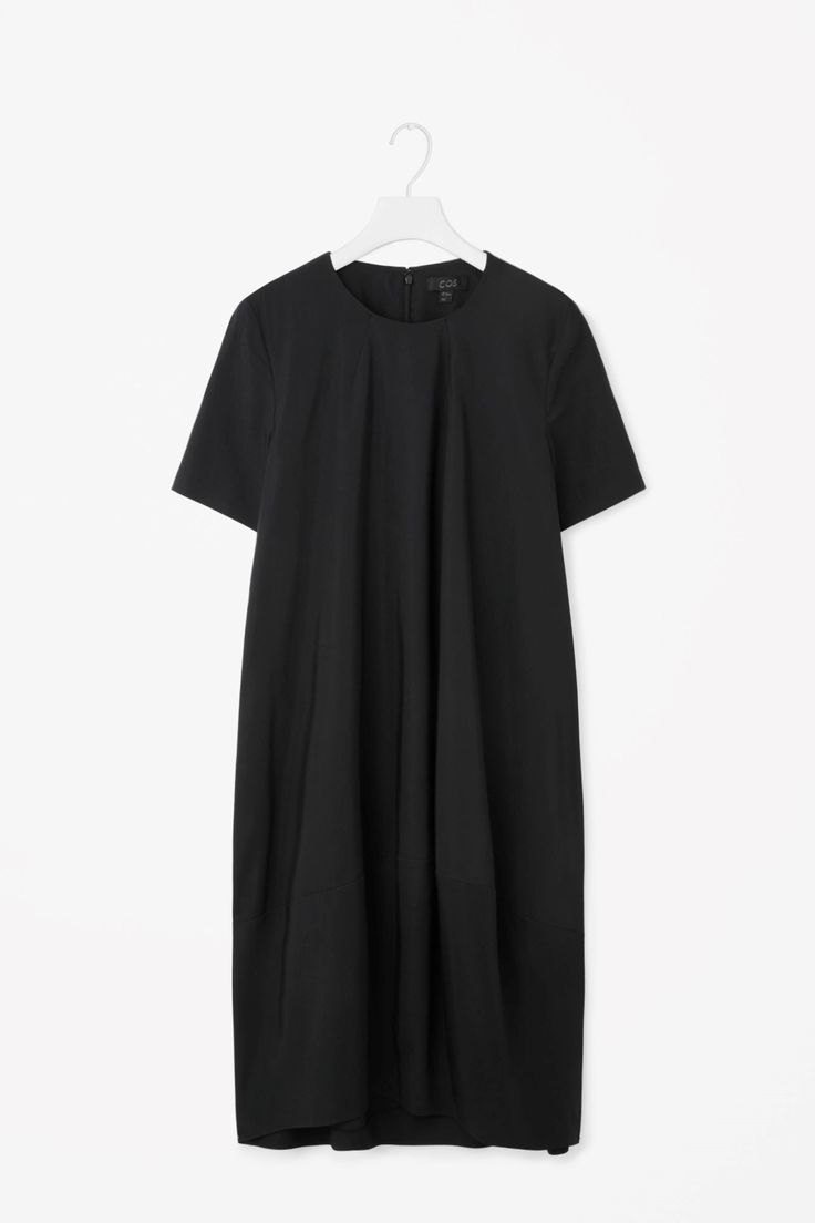 A voluminous shape with a concave asymmetrical hemline, this dress is made from a cotton-mix with a subtle ribbed quality. An A-line fit, it has a neat round neckline with dart seams, in-seam pockets and a hidden back zip.