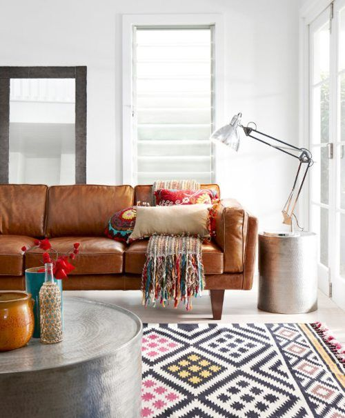 Crisp room warmed by brown leather couch and colourful carpet