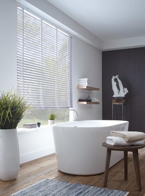 Ook voor in de badkamer witte jaloezieen van kunststof. Moderne badkamer met vrijstaand bad en huiselijke sfeer. Bestel eenvoudig en voordelig jaloezieen online bij Maatstudio.nl