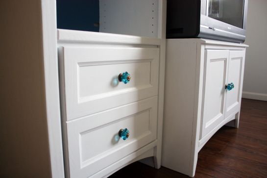 I recommend painting your media center white.  The dark wood is heavy and creates a large black hole.  I think white will freshen up the room. This link shares an inspirational how to, including priming and painting.