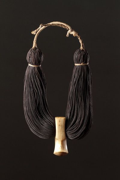 """Human hair, whale tooth. An antique Hawaiian """"Lei Niho Palaoa""""' - royal necklace of 8-ply braided human hair with a hook shaped sperm whale tooth pendant. Early 19th century. Hawaiian people exchanged locks of human hair as special tokens of power. Such necklaces were worn by rulers."""