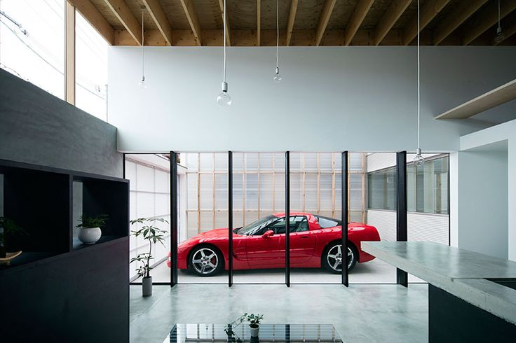the single-storey timber dwelling has been designed for a couple who are both car enthusiasts.