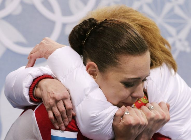 Adelina Sotnikova of Russia embraces her coach Elena Buianova in the results area after completing her routine in the women's free skate figure skating finals at the Iceberg Skating Palace during the 2014 Winter Olympics, Feb. 20, 2014, in Sochi, Russia. (AP Photo/Bernat Armangue)