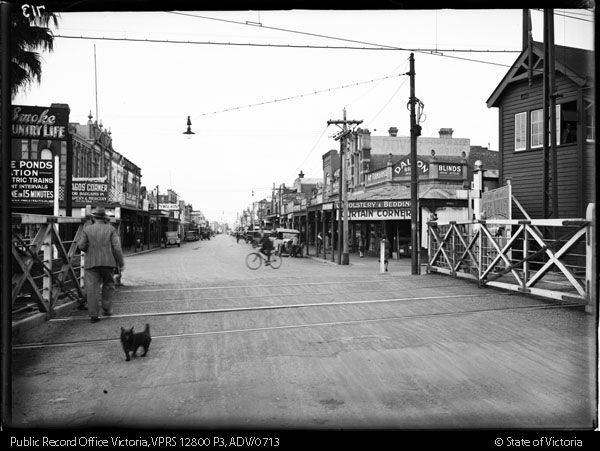 PUCKLE STREET MOONEE PONDS THROUGH LEVEL CROSSING . SIGNAL BOX ON RIGHT HAND SIDE FOREGROUND - Public Record Office Victoria