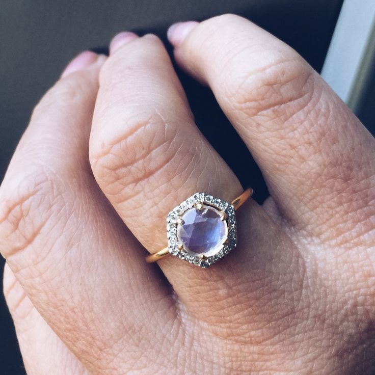 A rose cut moonstone is prong set, encased in a hexagon setting and surrounded…