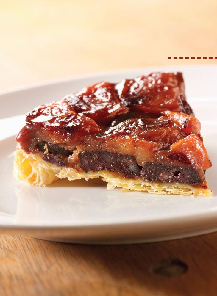 Bereiden:Verwarm de oven voor op 200°C. Beboter een pan met zware bodem, doe de suiker erbij en draai met de pan zodat de suiker zich mooi rondom verdeelt. Leg de appelpartjes naast mekaar op de bodem en druk goed aan. Zet op een laag vuur en karameliseer de suiker enkele minuten.Leg de stukjes zwarte pens op de appels.Gebruik het deksel van de pan om een ronde uit het bladerdeeg te snijden. Prik gaatjes in het deeg, dek de pan af met het deeg en druk zacht aan.