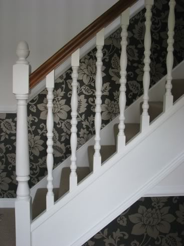 I can't tell you what the best type of paint is as I'm no expert, but I sanded back the stained and varnished wood on the bannisters of our staircase and galleried landing, then primed, undercoated and finally used Dulux Trade Diamond Satinwood on them. I didn't find it the easiest paint to use but it looks great and has kept as brilliant white as it was when I did it 2 years ago.