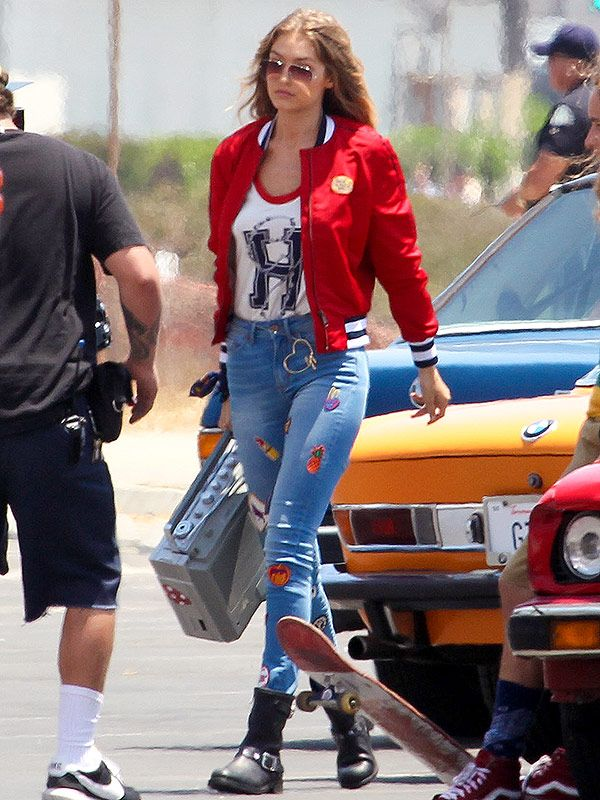 Gigi Hadid in a Tommy Hilfiger top, red bomber jacket and patch jeans