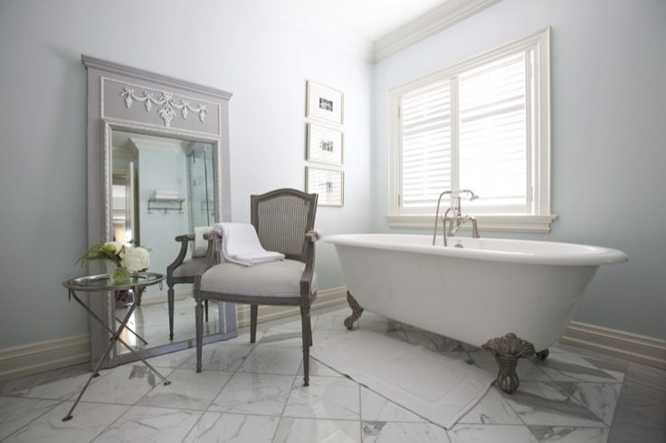 Stunning contemporary grey and white master bathroom with free standing tub, grey caned back chair, french style trumeau mirror and grey and white marble floors.