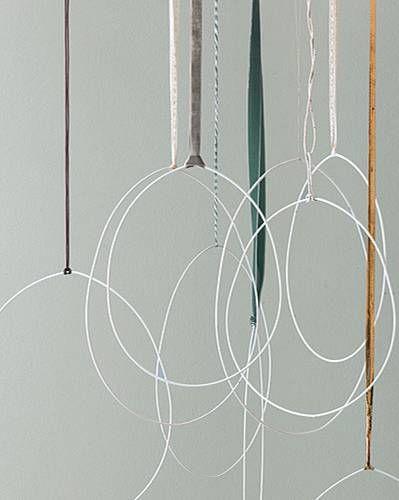 Fast schon Kunst: Für die Eier-Objekte brauchen wir große Ringe aus dem Bastelladen mit einem Durchmesser von 30, 35 und 40 Zentimetern (Rayher). Die Ringe werden mit der Nahtstelle nach oben ganz vorsichtig im oberen Drittel mit beiden Händen nach innen gebogen, so dass eine Ei-Form entsteht. Und dann mit langen Satinkordeln, Samtbändern oder Goldband dicht an dicht unter die Decke gehängt. Mit viel Freiraum und Abstand zu hohen Möbeln kommen die filigranen Silhouetten am besten zur…