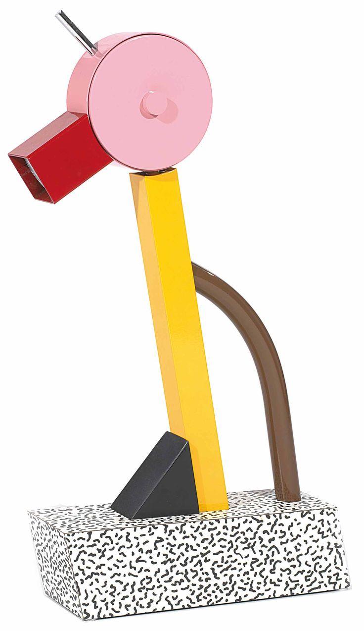"""Ettore sottsass (1917-2007) lampe """"tahiti"""", 1981, formant oiseau stylisé, base en plaqué de stratifié blanc à motifs de graffiti noirs, d'où s'élève un fût métallique jaune monté de biais soutenu par un triangle en bois noir, prise latérale cylindrique en métal brun. la tête de l'oiseau est formée d'un disque en métal rose, le bec cache-ampoule est formé d'un élément carré laqué rouge."""