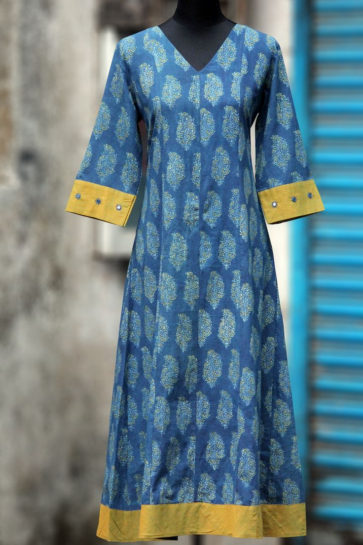 a long elegant indigo yellow ajrakh printed anarkali, with hand embroidery & traditional mirror work on sleeves. pair it with silk or chanderi dupatta for