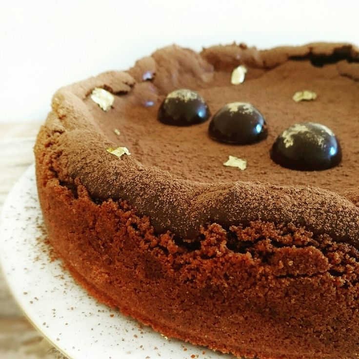 Baked Callebaut Chocolate Cheesecake, toped with chocolate semispheres and gold leaf.