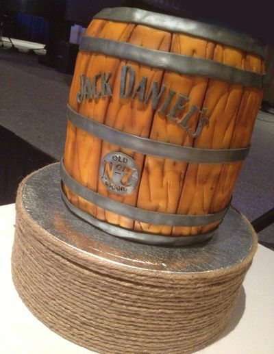 A groom's cake fit for a Southern gentleman!  Dark chocolate cake made to look like a Jack Daniel's barrel.  Set atop a rope adorned stand to complete the look.