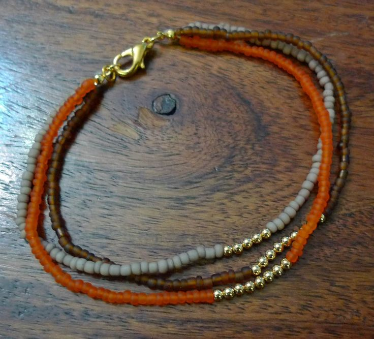 Armbånd af seed beads på perletråd med forgyldte perler.