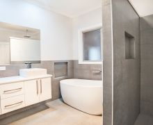 Freestanding bath, tiled inset shelf near bath and in shower. Walk-in shower with tiled walls. Ceiling-mounted shower head. Wall-hung vanity with above counter basins.