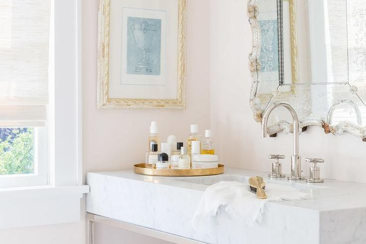 Blush pink bathroom boasting a dainty style and feel from Alyssa Rosenheck - Raquel Garcia Design - accented with a gold tray atop a marble sink vanity washstand.