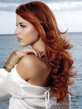 Model with red hair and golden jewelry.
