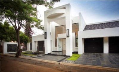 This modern Loius Liebenberg designed home is situated in the heart of Kosmos Village and takes your breath away as you enter the double volume glass entrance which showcases a stunning Swarovski Chrysal chandelier and double staircase. The house is split across several levels and has lots of glass windows allowing the natural beauty of the surrounds in