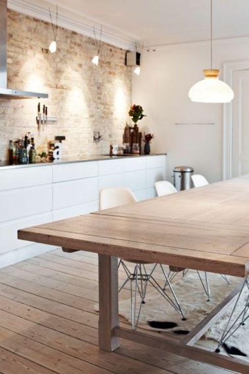 nowoczesna biała kuchnia ze ścianą z surową cegłą