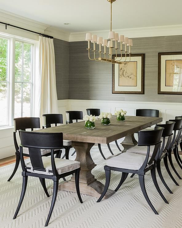 Transitional dining room features upper walls clad in gray grasscloth and lower walls clad in wainscoting alongside a Restoration Hardware Dumont Rectangular Dining Table atop a natural herringbone rug lined with Klismos Classic Side Chairs illuminated by a TT Linear Branched 10 Light Chandelier placed in front of windows dressed in cream curtains.