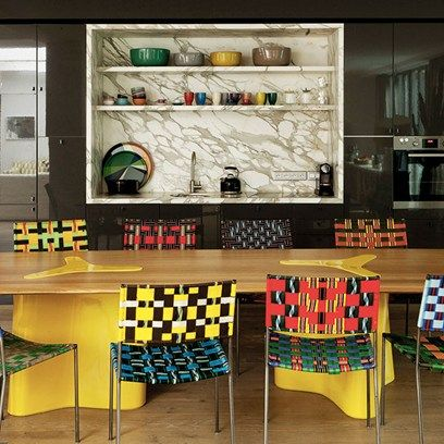 'Kitchens should be furnished like any other room. My kitchen has curtains, a rug and a velvet screen - I cannot live in a slick way,' says designer India Mahdavi. The Iranian-born architect and designer, who opened her studio in Paris in 1999, is famous for her dramatic interiors. This kitchen is furnished with India's 'Double Diagonale' table and Franz West chairs. A marble inset containing the sink and shelving punctuates the glossy dark panelling where the appliances are concealed.