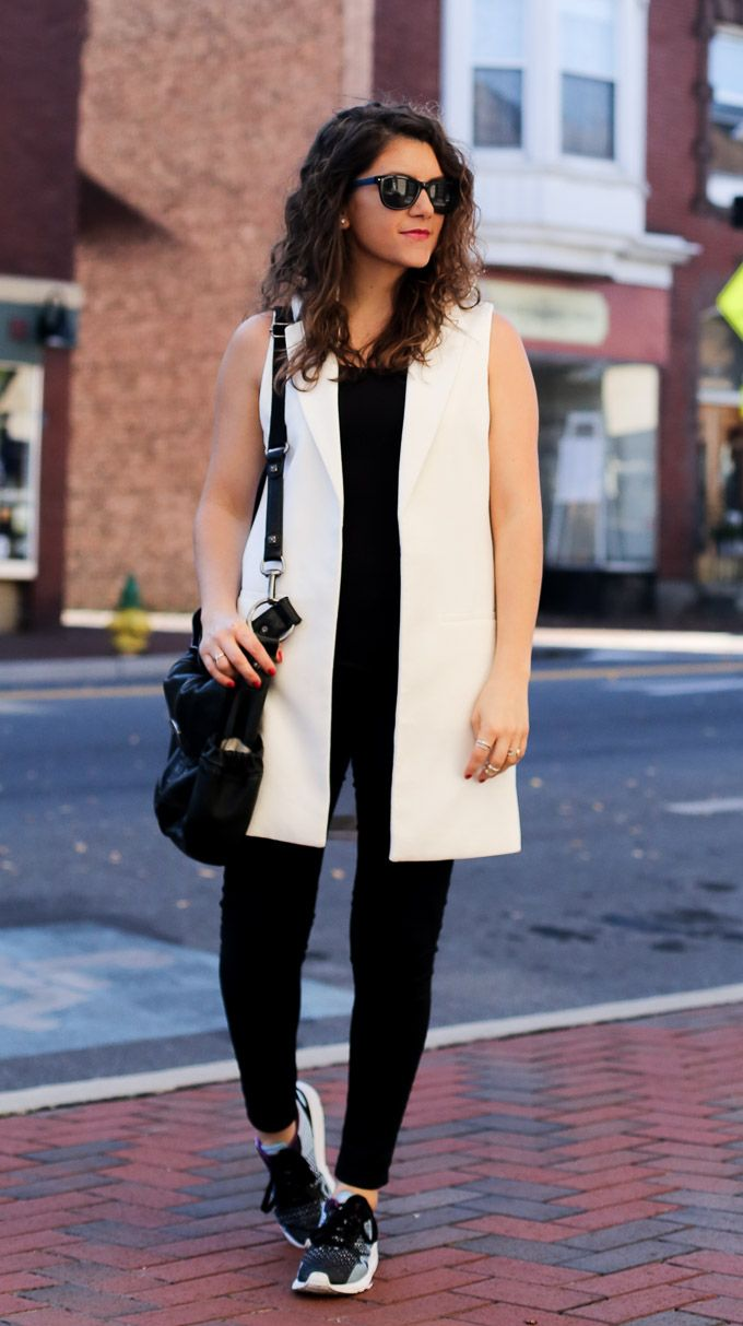 a sporty chic outfit with a tailored vest, black jeans and sneakers