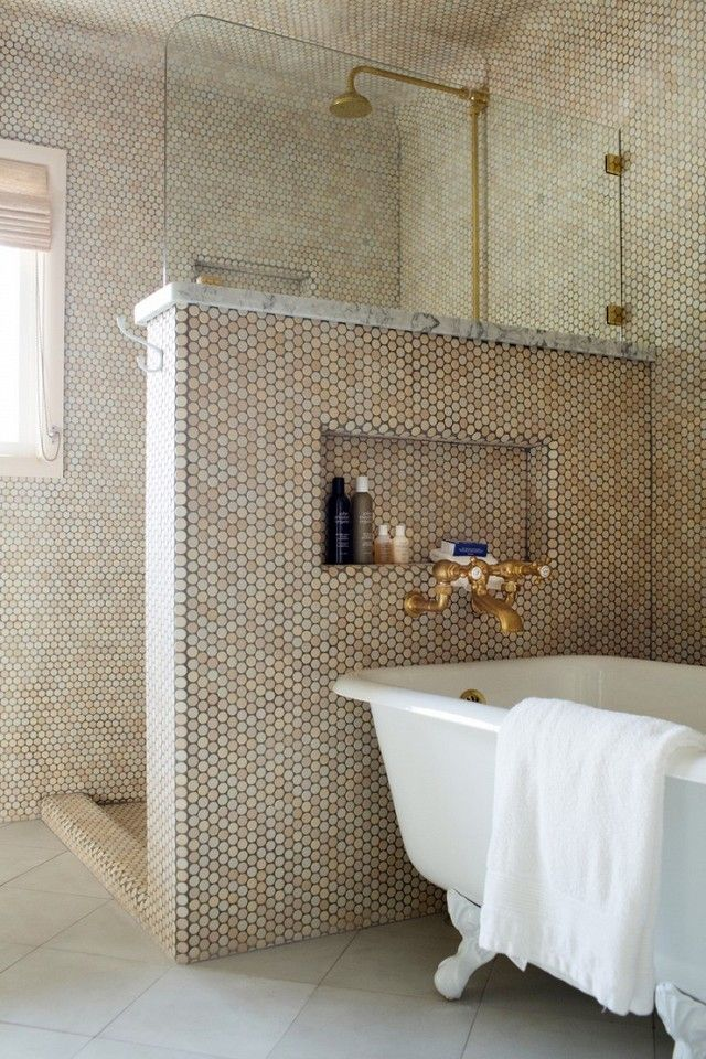 A bathroom with a sandy tone penny tile mixed with traditional brass fixtures and an inviting clawfoot tub