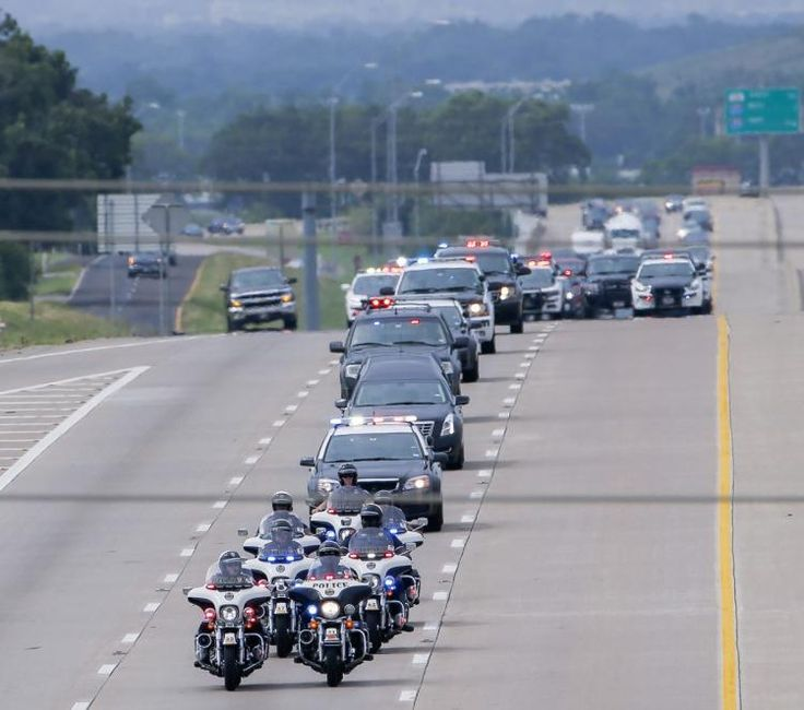 A procession of police cruisers and motorcycles escorted the body of slain DART Police Officer Brent Thompson to a funeral home 55 miles south of Dallas