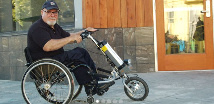 This is a powered handcycle that can be attached to a manual wheelchair and turn it into an electric trike.