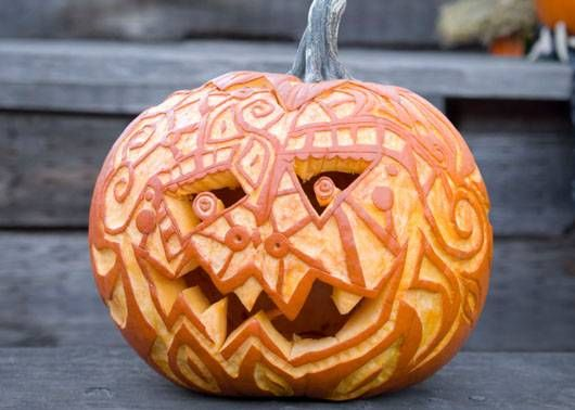 for those with an artistic edge this pumpkin carving idea is just for you this goofy jack o lantern is covered in shallow carvings that showcase the - Creative Halloween Pumpkin Carving Ideas