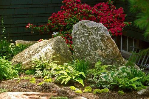 Beautiful stone arrangement. Excellent idea for rock garden.../instead of ferns desert plants in front of rock and bougainvillea behind it.